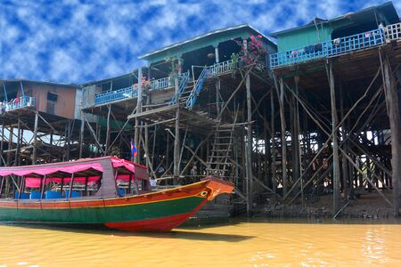 Red and green boat near stilt houses in a fishing village on Tonle Sap Lake in Cambodia.