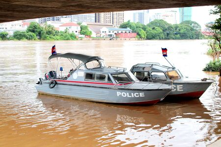 Two gray police boats on the Basak River, Phnom Penh, Cambodia Imagens