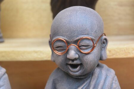 Gray Buddha statuette with spectacled orange frames, Cambodia, Southeast Asia