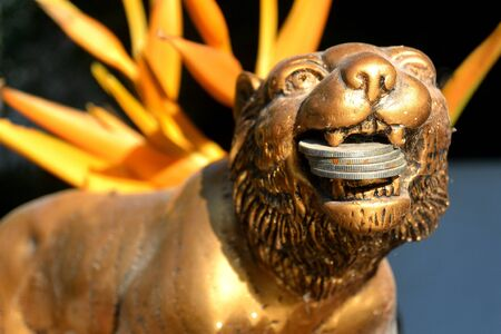 golden lion holds coins in its mouth against the background of an orange heliconia flower next to a sculpture of angkor wat close-up in cambodia Imagens