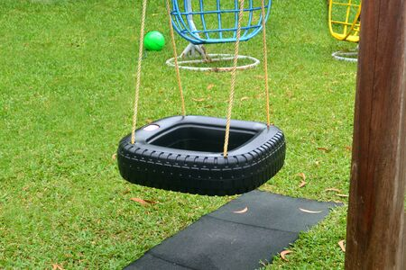 Swing in the form of a black square wheel on a green playground Standard-Bild