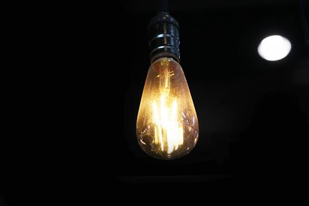 Yellow light bulb isolated on black background hanging on the ceiling 4 central
