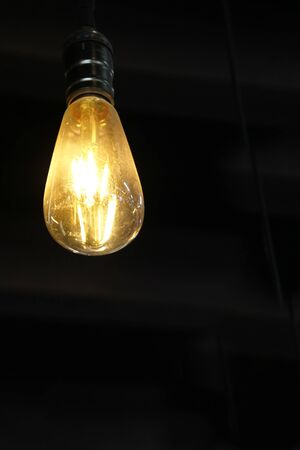 Yellow light bulb isolated on black background hanging on the ceiling 6 vertical