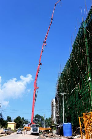 Red concrete pump near a green building, Cambodia, 2019 Stock Photo