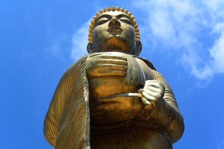 Golden statue of a standing Buddha waist-high against a blue sky, Sin Temple, Sihanoukville, Cambodia, Southeast Asia