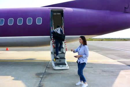 Confused woman with pasport in hands near airplane ladder