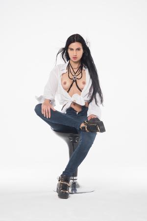 Schönes Mädchen posiert topless auf einem Stuhl in Blue Jeans Standard-Bild - 81863437
