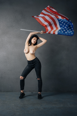 beautiful girl poses topless with american flag Stock Photo