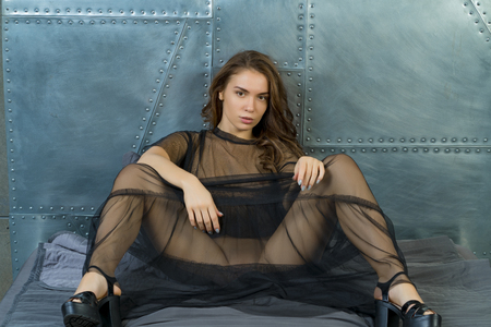 beautiful girl posing in a black transparent dress