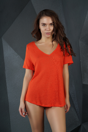 beautiful girl posing in an orange t-shirt in the studio Standard-Bild