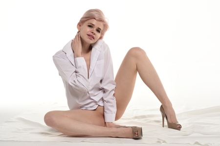 young beautiful girl sits on the floor in a white shirt in the studio