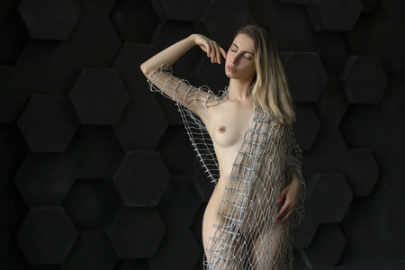 Hermosa jovencita posando en el estudio, de pie junto a la pared gris con un paño de malla Foto de archivo