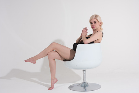 young beautiful girl posing nude in the studio, sits on a chair Standard-Bild