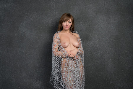 young beautiful girl posing nude in studio, standing near gray wall with cloth from mesh