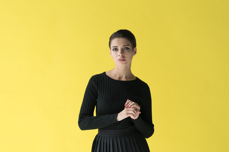 young beautiful girl posing in studio, standing in black sweater near yellow wall