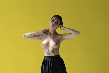 jong mooi meisje poseren in studio, staande in zwarte rok in de buurt van gele muur