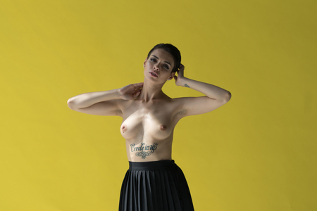 young beautiful girl posing nude in studio, standing in black skirt near yellow wall