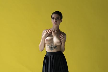 belle jeune fille qui pose en studio, debout près du mur jaune en jupe noire