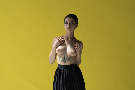 young beautiful girl posing nude in studio, standing near yellow wall in black skirt