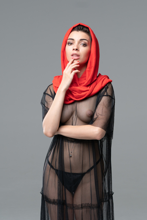 portrait of a young beautiful girl nude in the studio, standing in a black lingerie and a red kerchief Stock Photo
