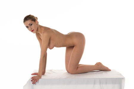 young beautiful girl posing nude in studio sitting on white table
