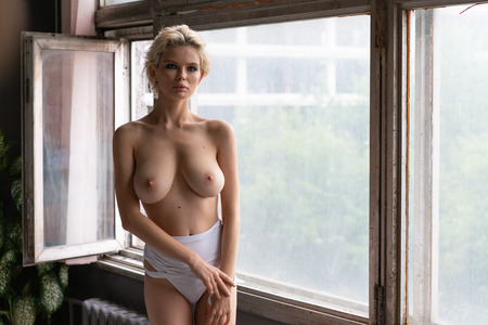 young beautiful girl posing in white underwear near the window