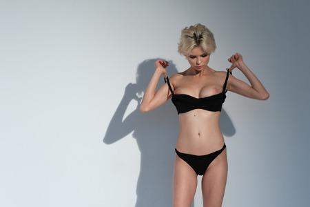 young beautiful girl posing nude in studio standing in black lingerie