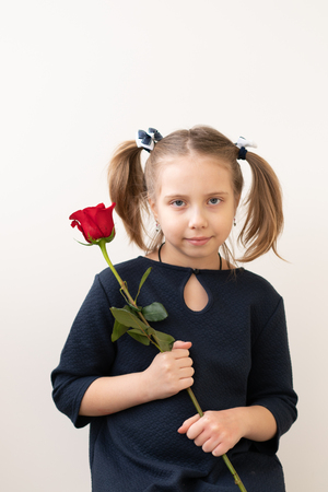 little girl stands with a red rose 스톡 콘텐츠
