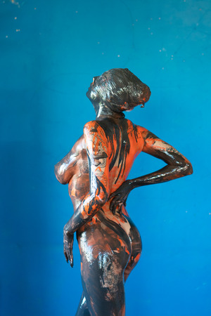 jeune belle fille posant de la peinture noire et orange