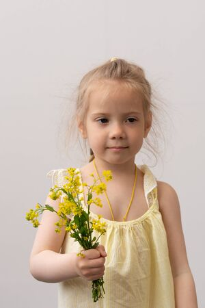 little girl stands with a bouquet of flowers