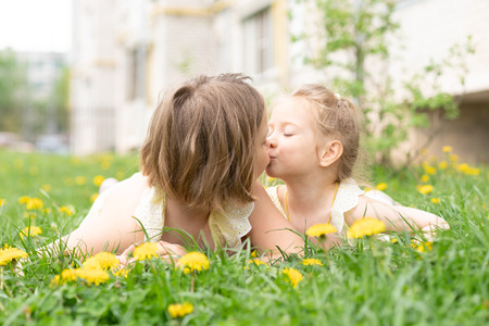 two girls are lying on yellow grass Stock Photo