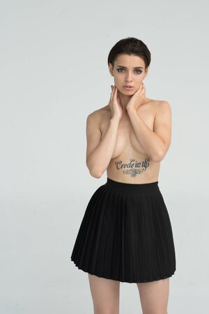 young beautiful girl posing nude in studio, standing in a black skirt Stock Photo