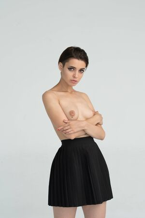 young beautiful girl posing nude in studio, standing in a black skirt Banque d'images
