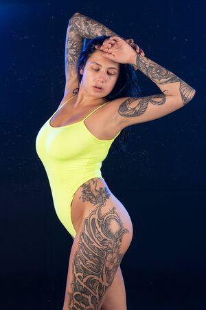 young beautiful girl posing in a yellow bodysuit Stock Photo