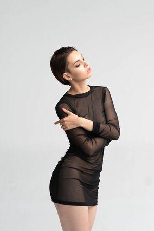 young beautiful girl posing in a black transparent dress