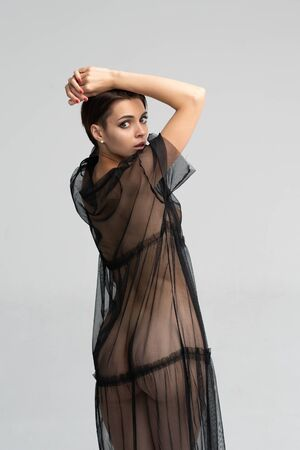 junges schönes Mädchen posiert im Studio, stehend in einem schwarz-transparenten Kleid