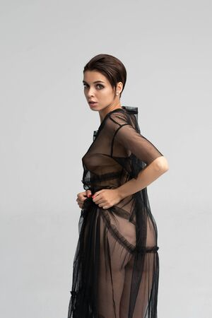 young beautiful girl posing in studio, standing in a black-transparent dress