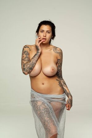 Young beautiful girl with tattoo pose nude in studio Banco de Imagens