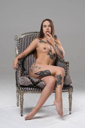 young beautiful girl posing nude in studio sitting on an armchair
