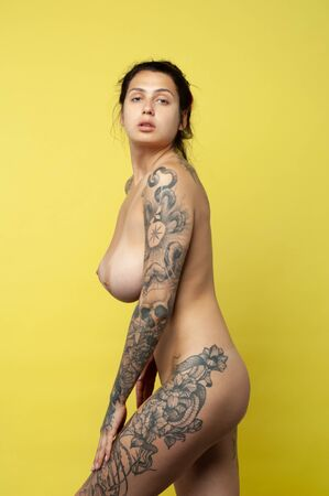 young beautiful girl with tattoo posing nude in studio