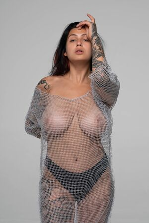 young beautiful girl with tattoo posing nude in studio