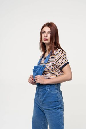 young beautiful girl pose in studio, stands in blue overalls near a white wall