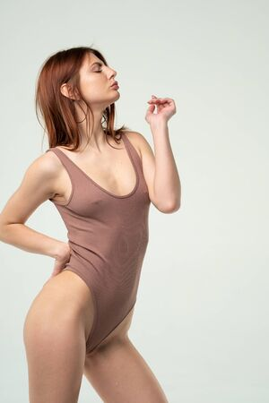 young beautiful girl posing in a brown bodysuit in the studio Standard-Bild