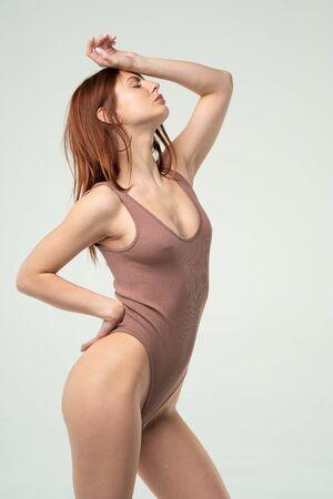 young beautiful girl posing in a brown bodysuit in the studio Standard-Bild