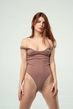 young beautiful girl posing in a brown bodysuit in the studio Banque d'images - 149586911