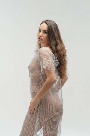 young beautiful girl posing in studio stands in a transparent dress near a white wall