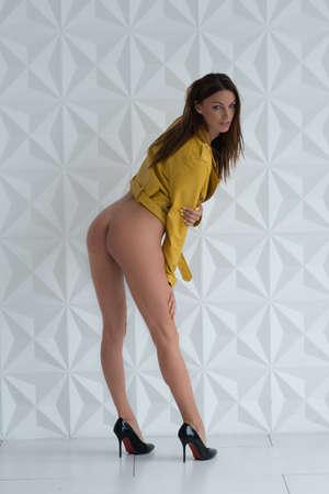young beautiful girl posing nude in the studio, standing in an orange jacket
