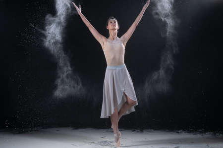 ballerina dancing in the studio with white flour, standing near a black wall Reklamní fotografie