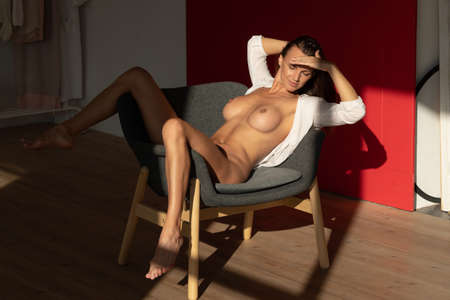 young beautiful girl posing nude in the studio, sitting on a chair Reklamní fotografie