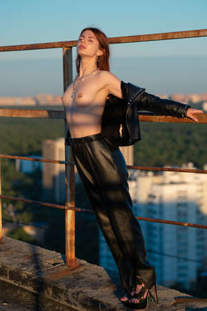 girl posing outside in the city, standing in black leather clothes Banque d'images